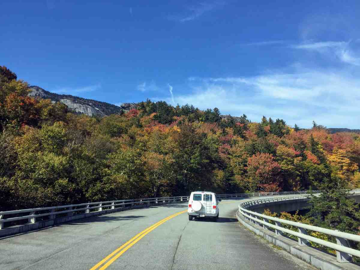 shows a winding mountian road, only one car ahead, leaves changing color, blue skies