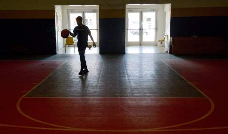 shows a boy in silhouette who's playing basketball indoors at a foster care group home