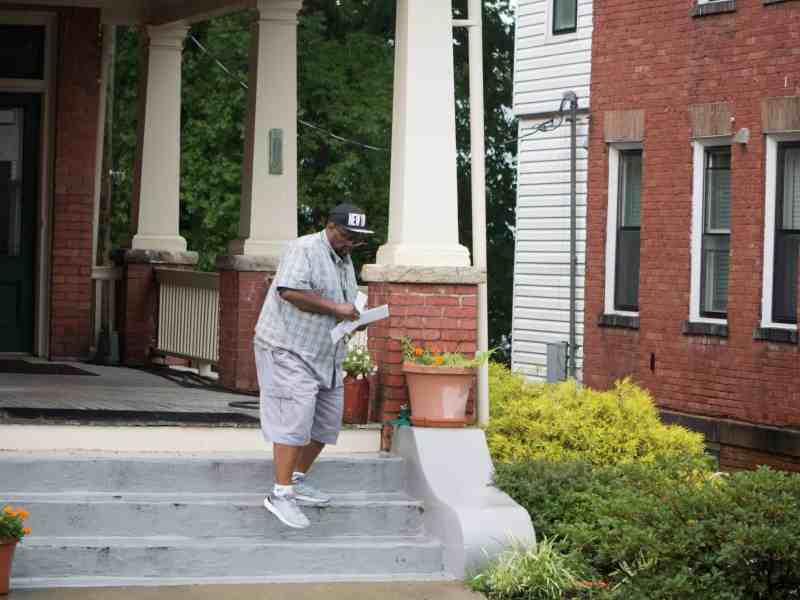 man stands on the steps of an old brick house, checking envelopes from the mailbox