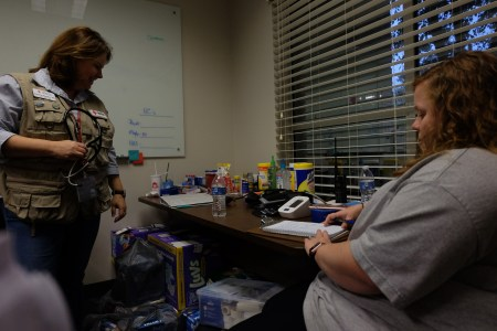 a woman standing up, wearing a Red Cross vest looks down at a table covered with medical supplies. Another woman is sitting with a pad of paper and a pen.