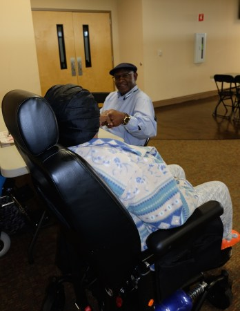 see a woman from behind who is in a wheelchair talking to an african American man in a jaunty cap