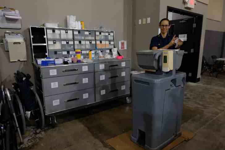 a smiling woman dries her hands at a portable sink, a big grey cabinet of medical supplies sits next to her