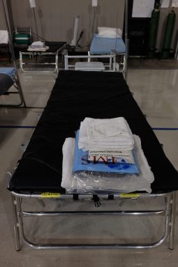 a simple black cot, with a stack of linens and chux