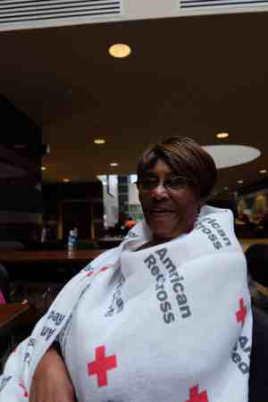 """shows a woman wrapped in a blanket that reads """"American Red Cross"""""""