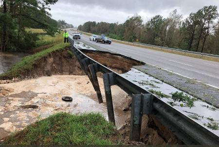 Shows a major highway that's completel undermined, part of the roadway has fallen away.