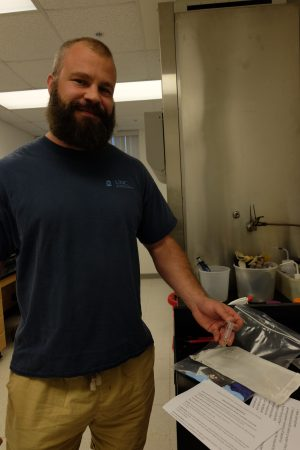 shows a burly bearded guy in shorts and a t shirt inside a lab, he's displaying some equipment on a table