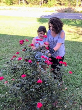 A woman shows her young daughter how to tend to a rose push