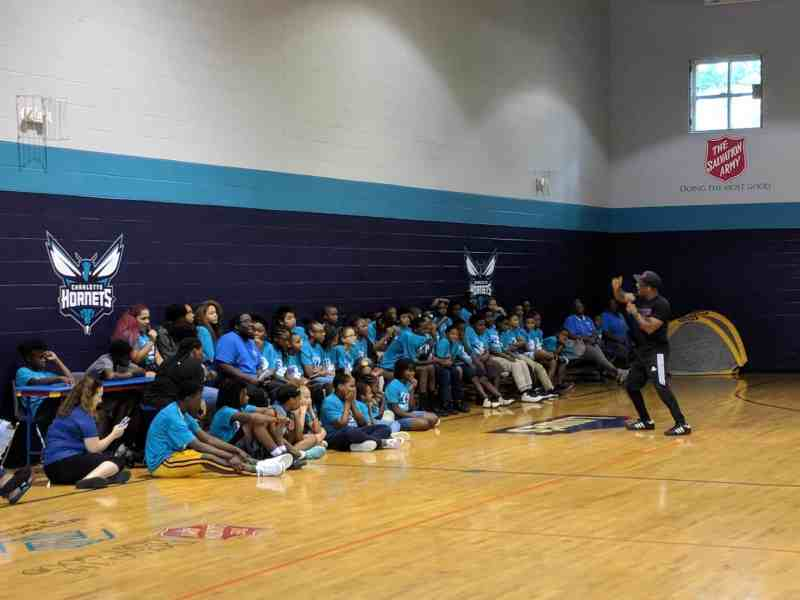 A few dozen children in bright blue t-shirts sit in a gym facing a man with a microphone who is in the middle of rapping to them.