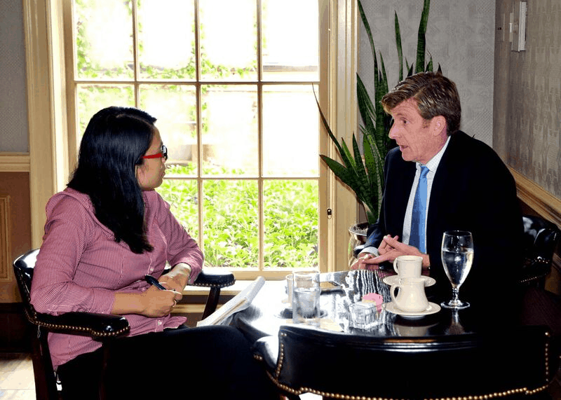 A woman interviews a man in a suit sitting at a black wood table with coffee and water in front of a window with greenery.