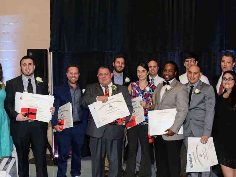 A group of people in professional clothes stand together presenting their graduation certificates.