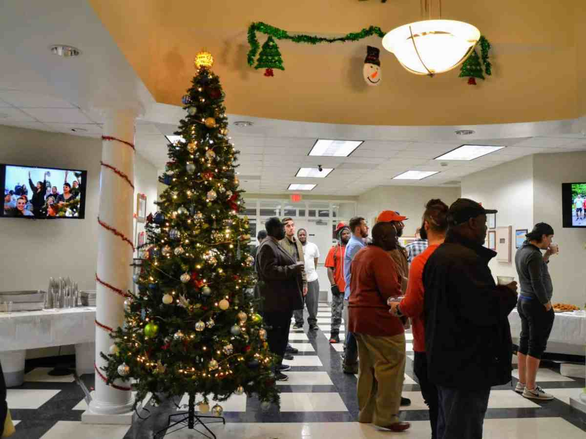 People stand in a open foyer with a Christmas tree and tables of food.