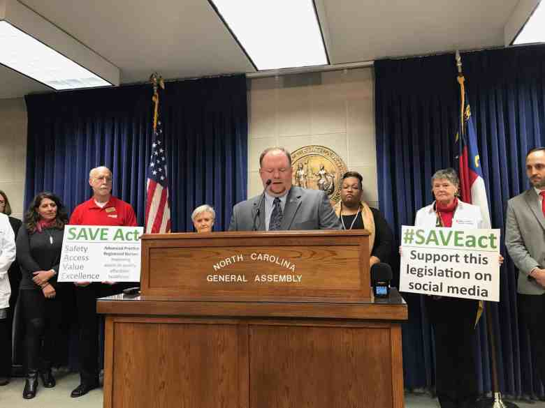 shows a man at a podium, flanked by people holding signs.
