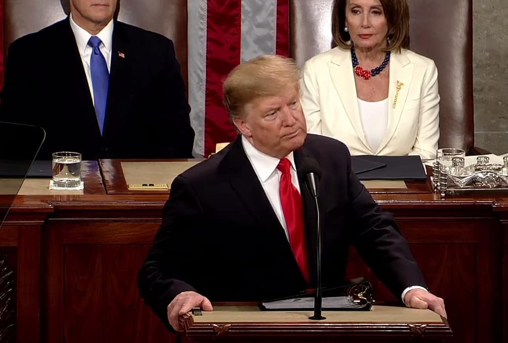 donald trump stannds at podium, Pelosi and pence visible behind him.