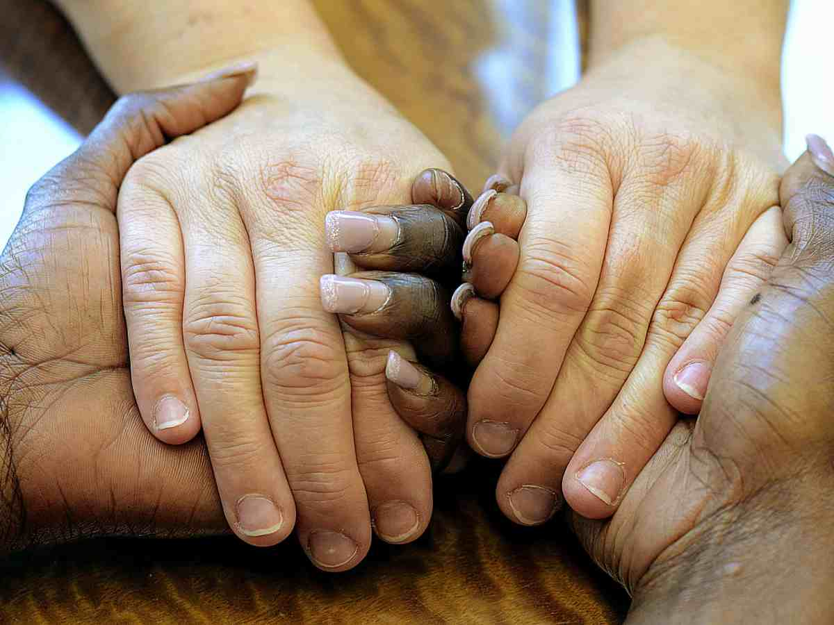 shows hands, black and white clasped as a proxy to talk about the pain that comes from domestic violence.