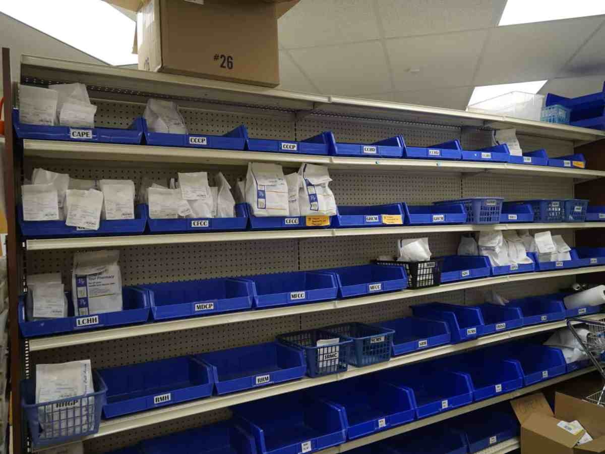 A wall of blue bins, each labeled with a code, some are full of prescription bags