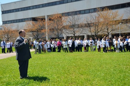 White Man in suit speaks to large group of people in white medical coats