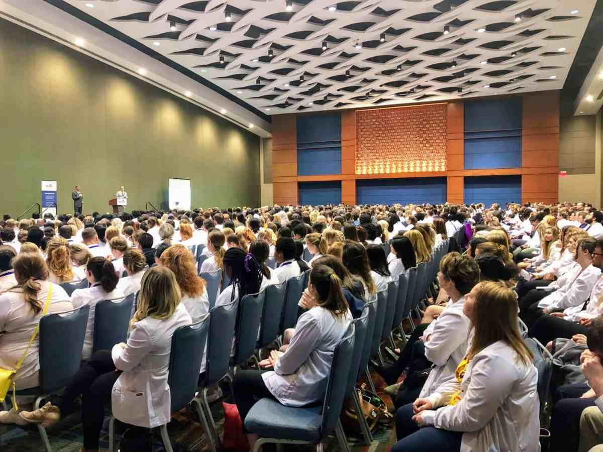 rows of nurses in white coats sit facing a speaker