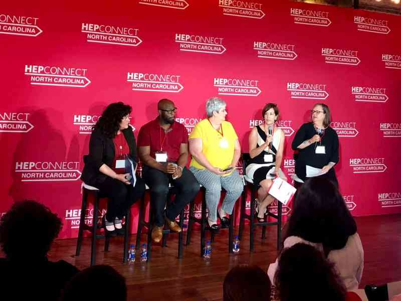 five people sit on stools with red backdrop behind them discussing hepatitis C prevention