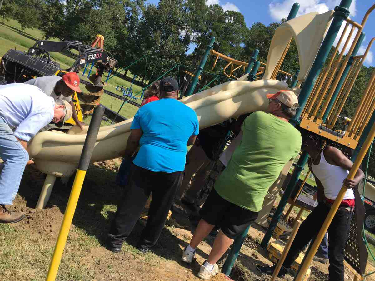 A group of people is placing a playground equipment on the ground, behind them are trees and an excavator. This is part of their efforts to address obesity.