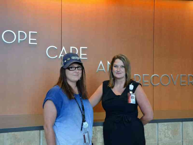 two women who are peer support specialists stand in front of a wall