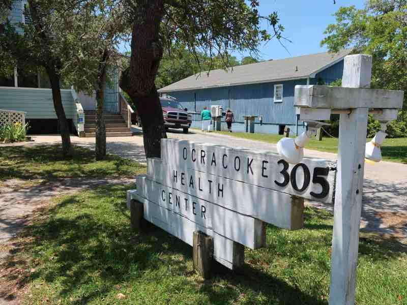 in the foreground, a sign reading Ocracoke Health Center, with buildings and people walking away in the background