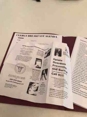 """shows some folded papers. One reads, Opiate Overdose Prevention and Survival and the other reads """"Clergy Breakfast Agenda"""""""