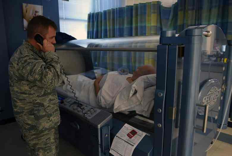 shows a man laying in a hyperbaric oxygen therapy chamber. Another man in military fatigues stands outside the chamber, talking on the telephone.