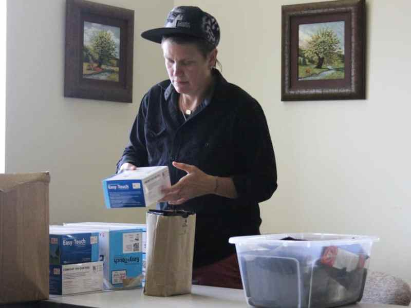 A person in a sports cap holding a needle box to be packed away and delivered to needle exchange participants. Dunlap says they meth use never went away in Haywood County.