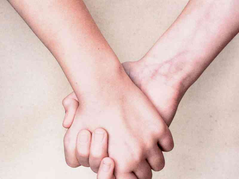 Two hands clasped together to signify peer support