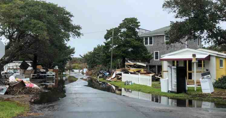 shows a street on Ocracoke wet with puddles with construction and demolition debris piled head high on the roadsides