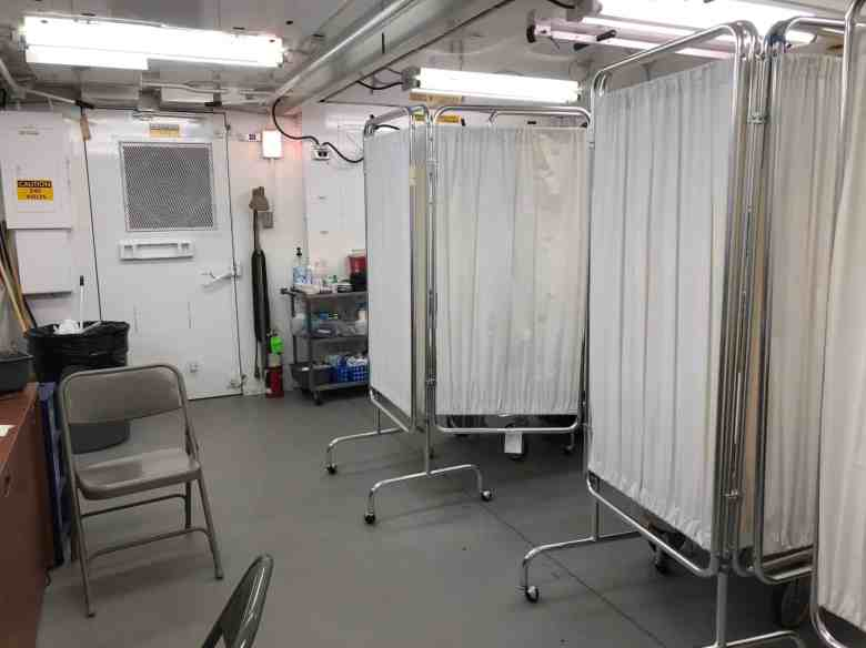 Shows a cramped room with portable cloth dividers on casters