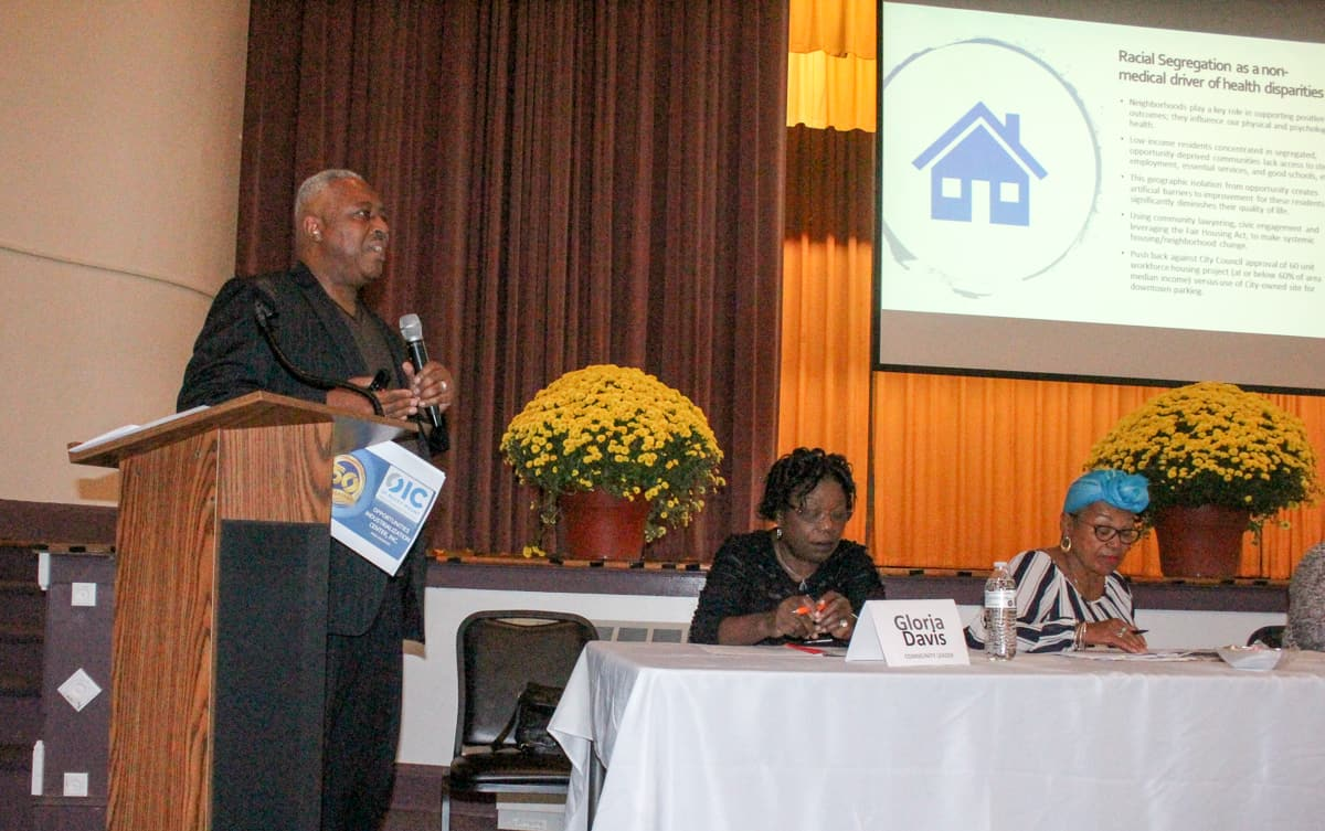 An African American man stands in front of a podium, behind him there's a slide about disparities. There are also two women sitting in front of a table at his side. This was a press conference to discuss OIC of Rocky Mount and among other topics, medicaid transformation came up.
