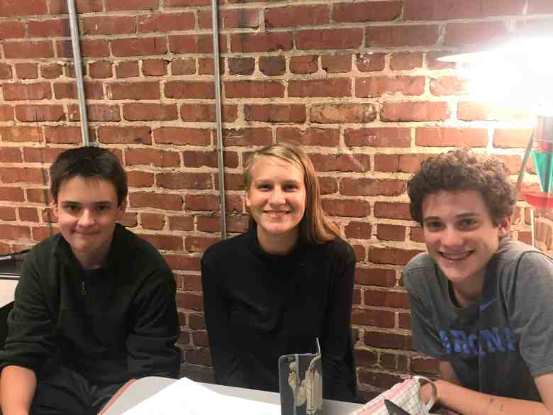Three students against a brick wall at a school in Raleigh. They are doing a project on PFAS