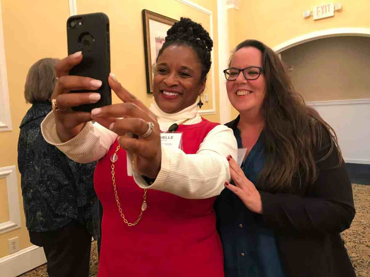 Two women take a selfie at a conference where they talked about medicaid transformation