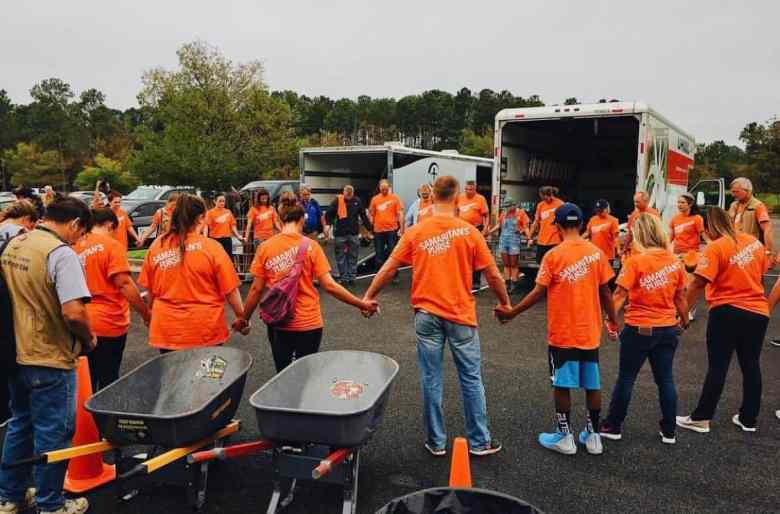 Several dozen people in orange T-shirts hold hands in a prayer circle