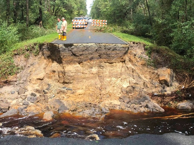 Rescuers in boots on broken pavement and deep ravine created by Hurricane Florence