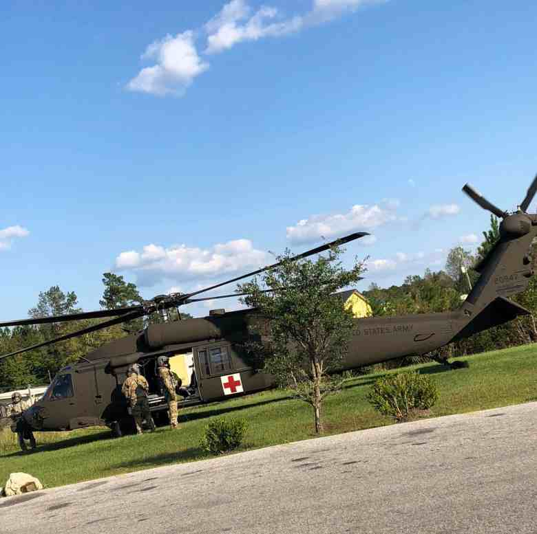 Military helicopter with a red cross on the side landed for rescue