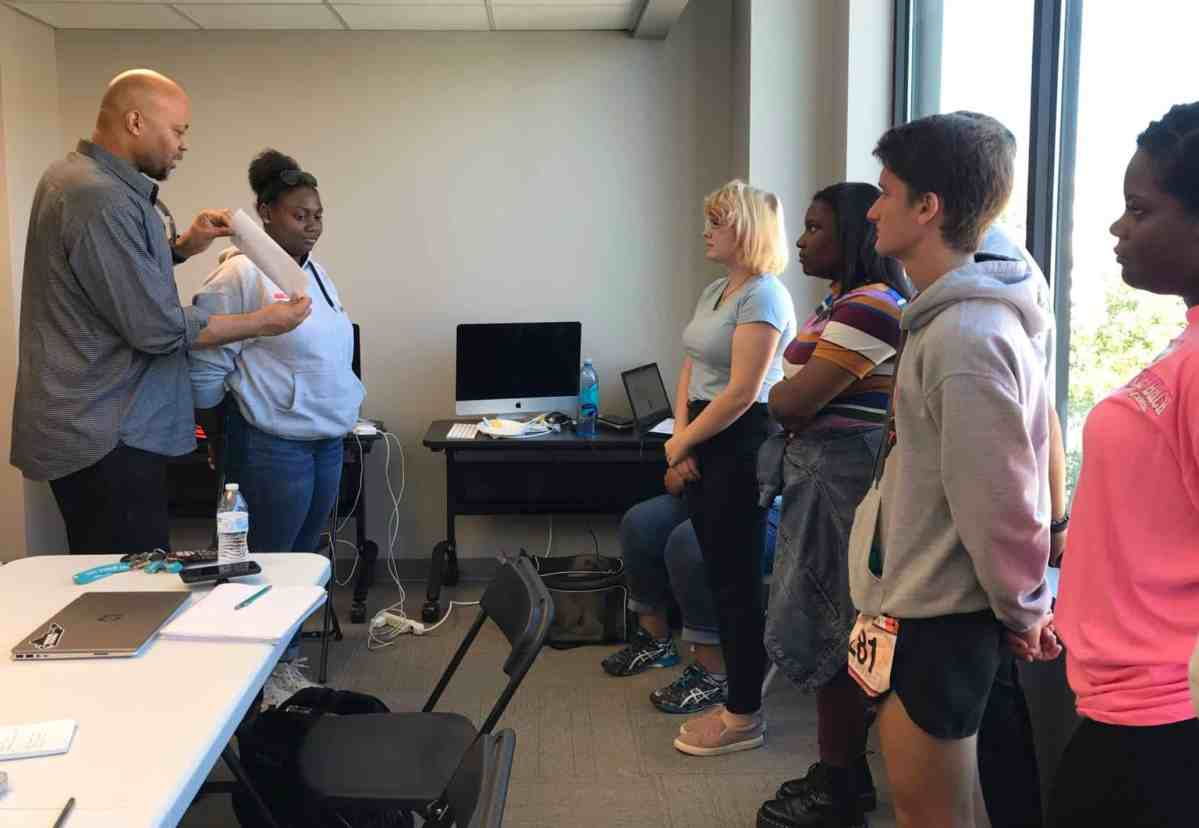 An older man instructs a group of young people during a Florence resiliency workshop