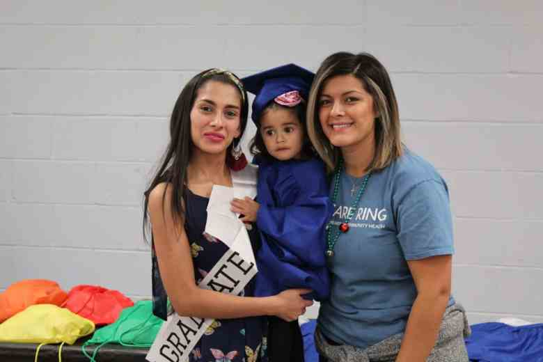 """A mother with a """"graduate"""" sash, toddler in a graduation gown and a nurse smiling"""