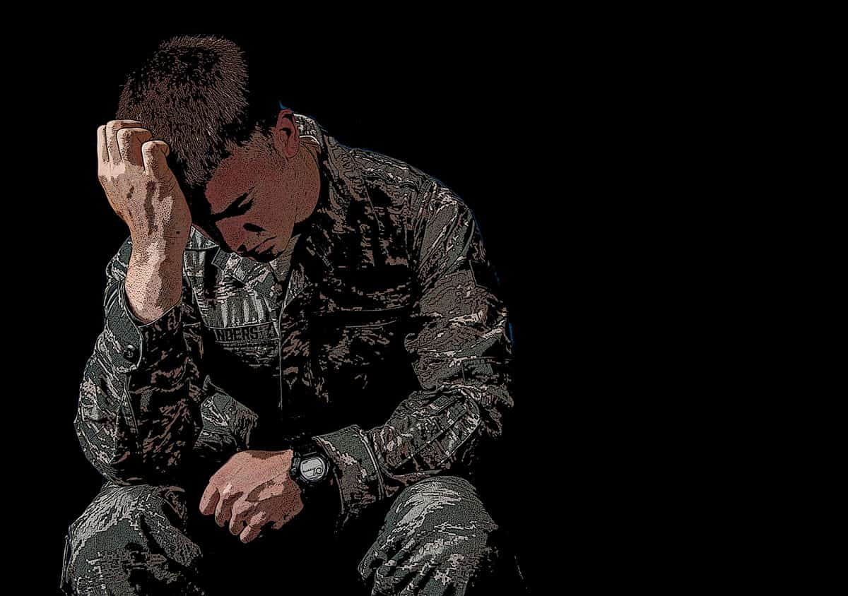 shows a soldier with his head in his hands, used to represent post traumatic stress disorder / PTSD