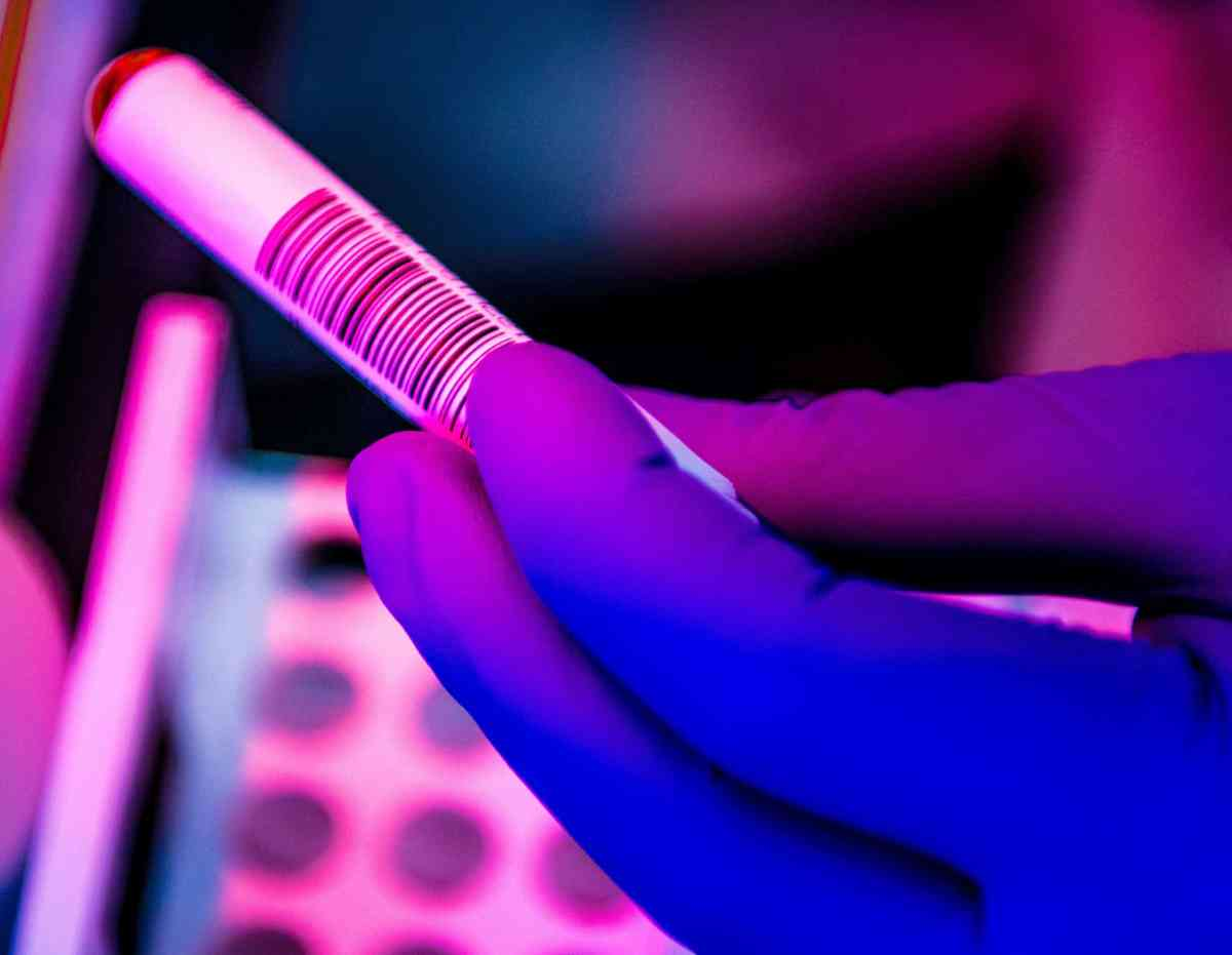 hands hold a tube of blood as a proxy for coronavirus tests and research