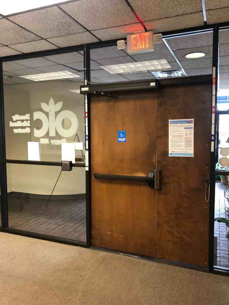 A clinic door with a COVID-19 sign