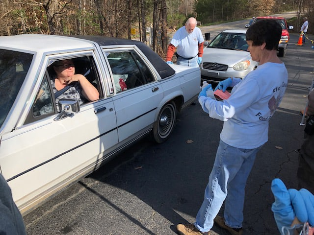 A photo of a food bank worker with gloves talking to a participant who is staying in the car, as a measure of social distancing. This is one way that food banks in NC are minimizing social contact during the COVID-19 outrbeak.