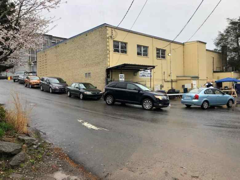 A line of cars near a large yellow building in Haywood County. Using car pickup is one measure of social distancing.