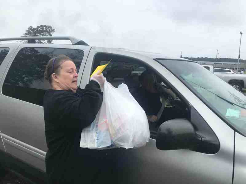 Ann Hall delivers free lunches to Brittany Chavis Tuesday, March 17, at Cape Fear High School in Cumberland County. This is part of an effort to provide free lunch to children during COVID-19