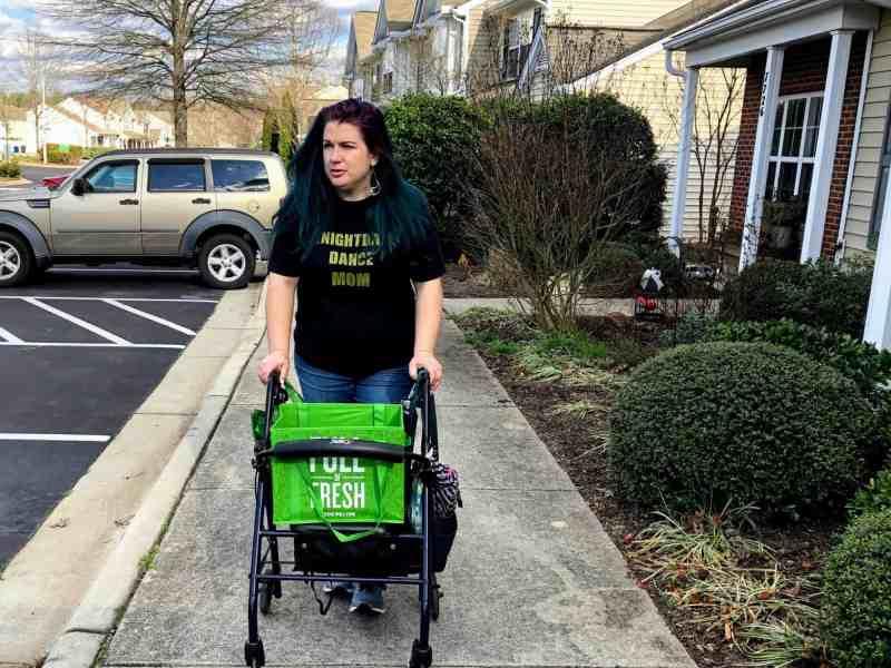 woman walks down sidewalk with the help of a walker. She has chronic pain