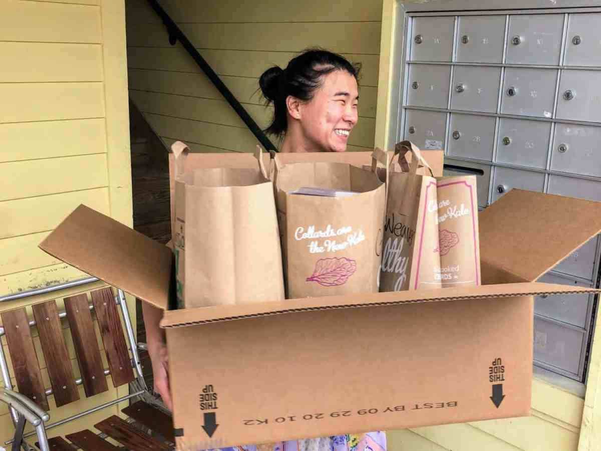 mental health worker carries large box with paper bags in it. She is a worker at Club Nova, which helps people with mental health needs.