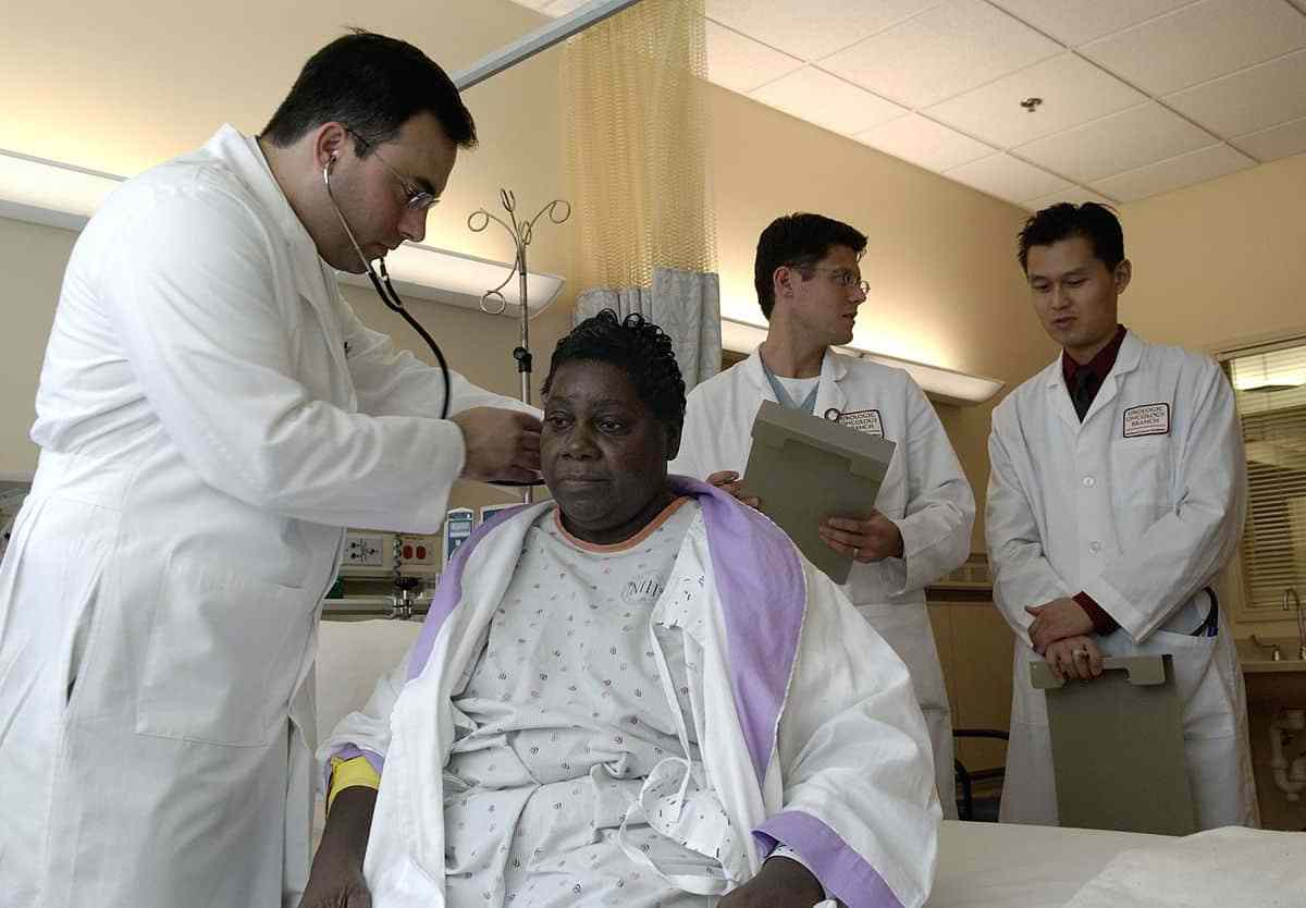 young Latino physician examines an older African American woman patient.