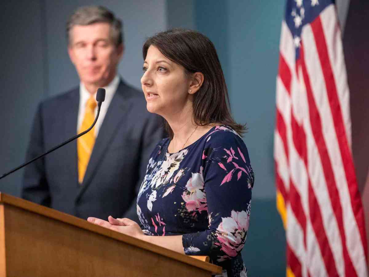 Sec. Mandy Cohen speaks at a podium and Gov. Cooper is at the background blurred. They are at a briefing about coronavirus.