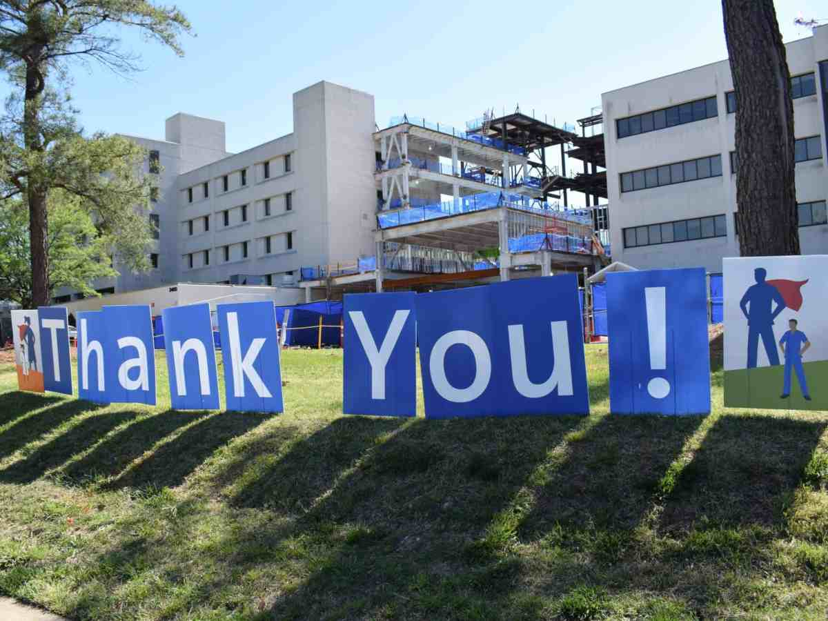 A photo of thank you banners in front of the Duke Raleigh hospital campus. The signs are to celebrate healthcare workers responding to the Coronavirus pandemic.